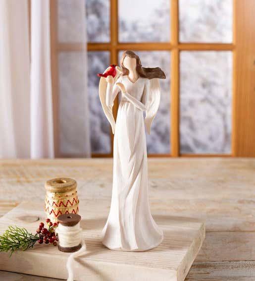 Image of an angel figurine holding a cardinal. Shop Angels & Santas